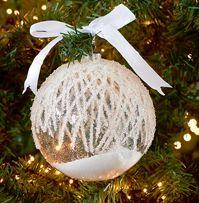 Julekugle i glas med frost og sne indeni